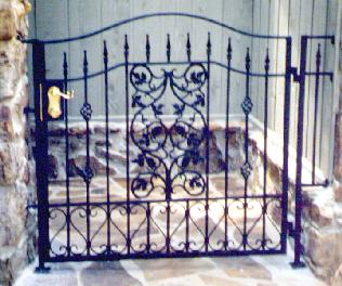 wrought iron walkway gate with grape pattern and brass deadbolt