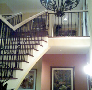 curved wood handrail on a wrought iron stairway railing